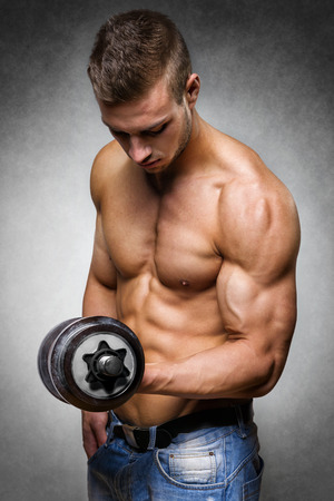 pecs: Young man with well trained body, biceps, abs and pecs holds a dumbbell