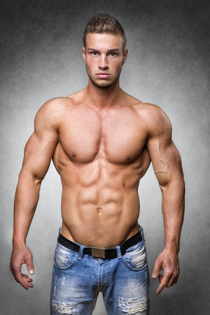 denim trousers: Young man with well trained body, biceps, abs and pecs and wearing a denim trousers Stock Photo