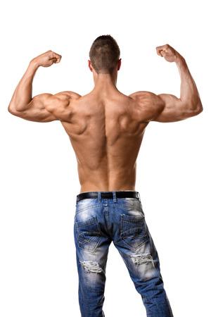Terug van een jonge man met een goed getraind lichaam, triceps, lats en ruitvormige spieren en het dragen van een denim broek