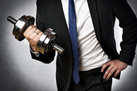 Image of a businessman with dark suit and silver dumbbell
