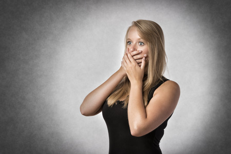 shocked: Blonde shocked woman holding anxiously the hand over mouth Stock Photo