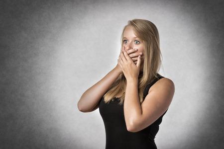 boca abierta: Mujer sorprendida rubia que sostiene con ansiedad la mano sobre la boca