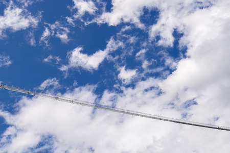 traverse: Image of a chain bridge in high altitude with blue sky and clouds