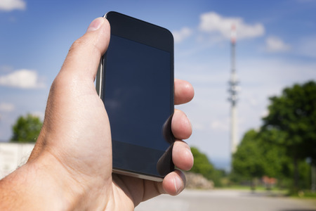 Image of hand with mobile phone and broadcasting tower in the background