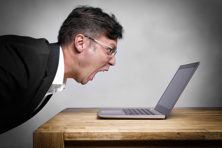 Man sitting at the table and screaming at his laptop Reklamní fotografie