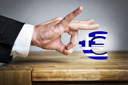 arrogancia: Hombre de negocios que dispara con su dedo de la Muestra euro con la bandera griega de una tabla Foto de archivo