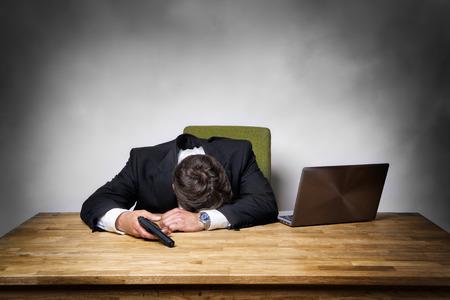 Overworked businessman in office with gun