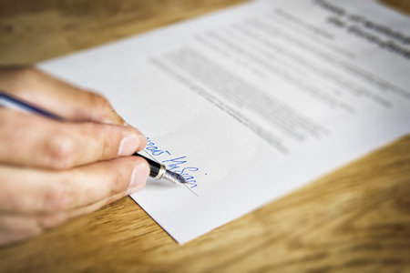 legal office: Image of a hand that signs a business contract