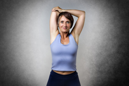 ropa vieja: Mujer de mediana edad guapo haciendo un ejercicio de estiramiento Foto de archivo