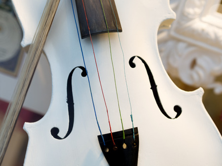 fiddlestick: Image of a white violin with fiddlestick