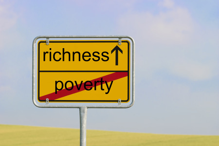 richness: Yellow town sign with text poverty richness