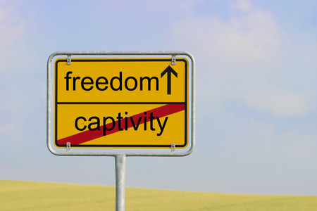 freeing: Yellow town sign with text captivity freedom