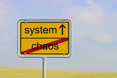 order chaos: Yellow town sign with text chaos system