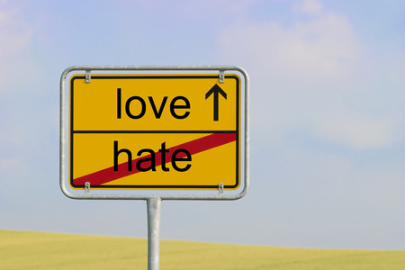 highway love: Yellow town sign with text hate love