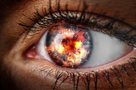 Close-up van het oog van een vrouw die met vuur