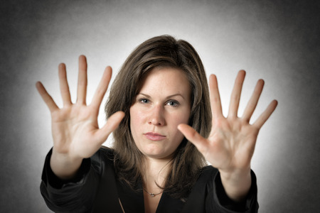 no person: Business woman in black suit holds both hand up to stop someone or something Stock Photo