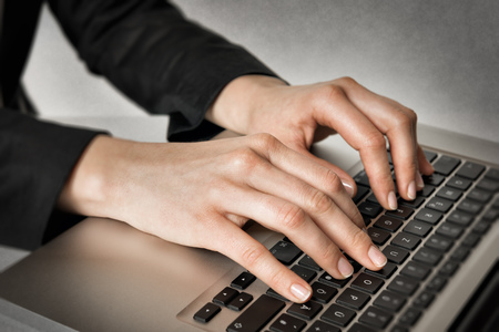 Closeup of hands of a business woman typing on a laptop
