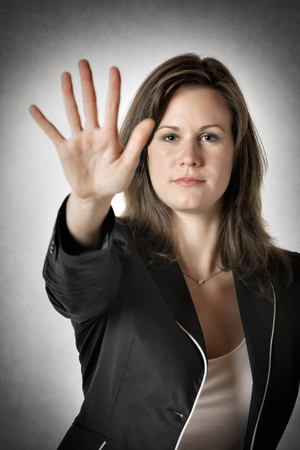 no person: Business woman in black suit holds her right hand up to stop someone or something Stock Photo