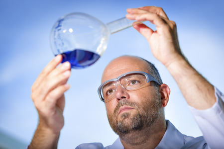 safety goggles: Chemist with safety goggles examining a blue liquid