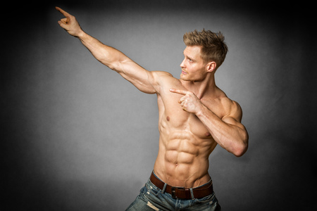 denim trousers: Blond young man with well trained body, abs and pecs and wearing a denim trousers look to the left