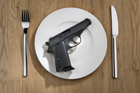 white plate: pistol on a white plate with knife and fork Stock Photo