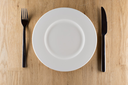 shiny black: Plate, knife and fork on a wooden table
