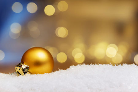 artificial lights: Image of a golden bauble on artificial snow with bokeh lights in background and free space Stock Photo