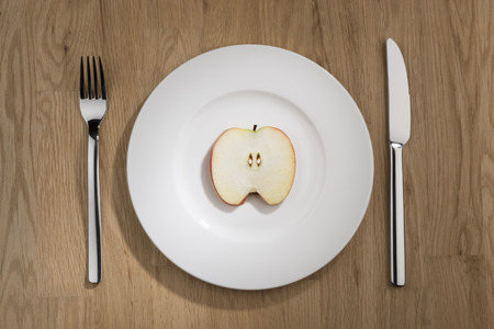apple slice: Image of a apple slice on a white plate with fork and knife