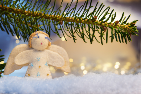 artificial lights: Image of a branch with felt angel on artificial snow and bokeh lights in background