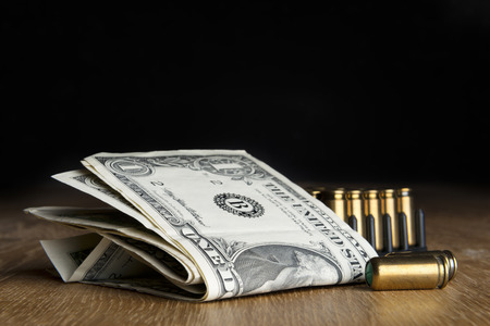 terrorism crisis: Image of dollar bills with pistols cartridges on a table Stock Photo