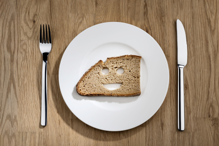 hunger: Image of a slice bread with smiling face on a white plate with fork and knife