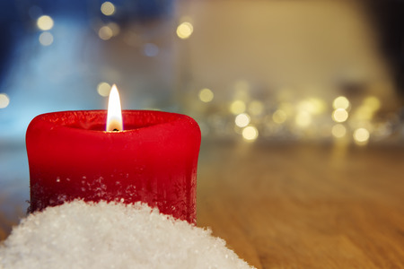 artificial lights: Image of a red burning candle with bokeh lights in background and free space