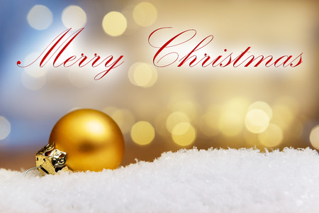 artificial lights: Image of a golden bauble on artificial snow with bokeh lights and text Merry Christmas Stock Photo