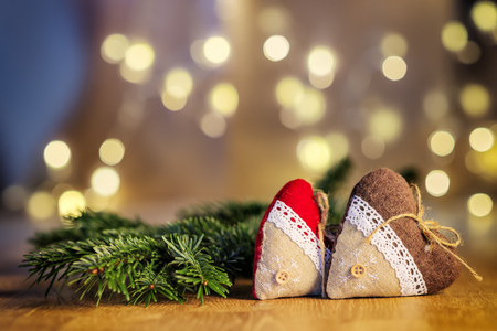holiday lights display: Image of two decoration hearts on wooden table and blur lights in background with free space