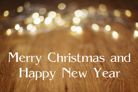 christmas lights display: Image of a wooden table with bokeh lights in background and text Merry Christmas and Happy New Year Stock Photo