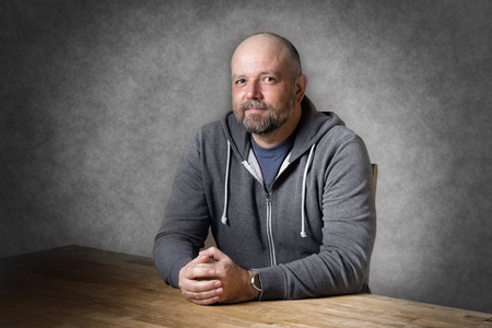 unshaven: Portrait of a friendly looking, balding and unshaven man sitting on a wooden table
