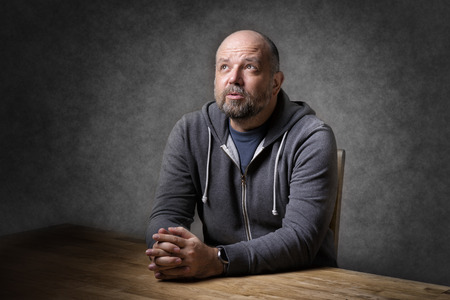 unshaven: Portrait of a thoughtful looking, balding and unshaven man sitting on a wooden table