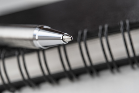 Closeup of a pen on a black organiser with leather cover