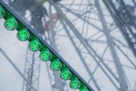 Green lights of a big wheel on a fair in Thun in Swiss Stock Photo