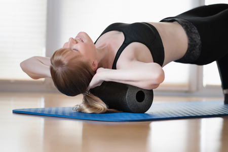 Young girl doing sport excercise with fascia roll Фото со стока