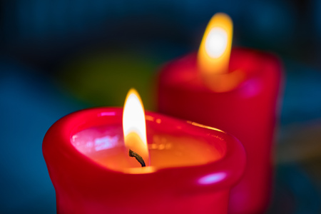 Image of two red burning candels on a table Archivio Fotografico - 115563828