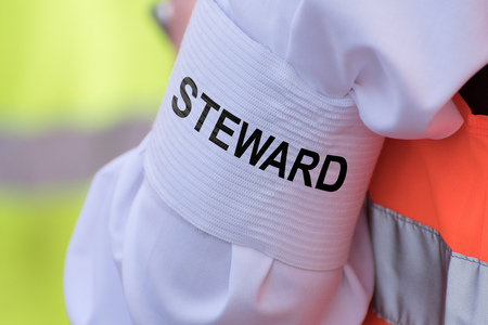 "Detail of an armband on the upper arm with the text ""STEWARD"""
