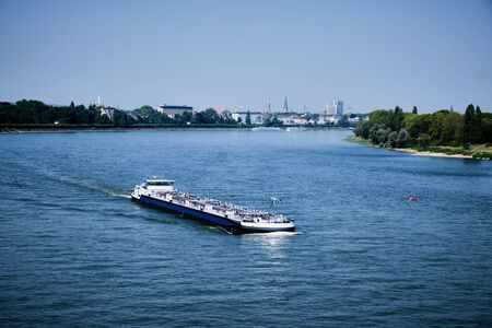 Image of view to Bonn and a cargo ship on river Rhine in summer Stock fotó
