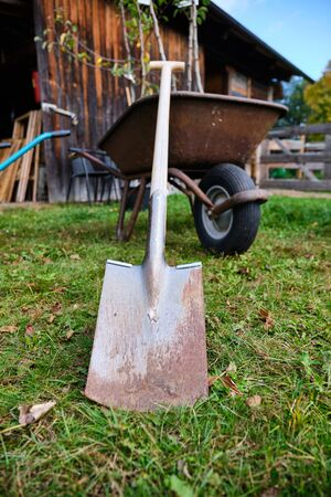 Shovel leans against a wheelbarrow in front of a shed in Bavaria, Germany Stock fotó