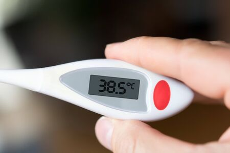 Picture of a fever thermometer indicating 38.5 degrees Celsius Stock fotó