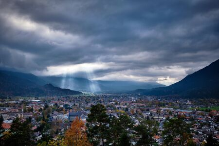 View to Garmisch-Partenkirchen in Bavaria, Germany with clouds and sunbeams on a cloudy day in autumn