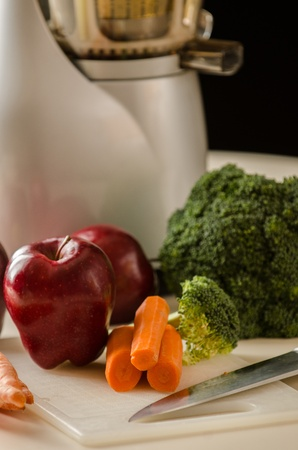 Photo of Apples Carrots and Broccoli in Front of a Juicer