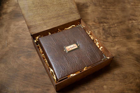 gift photo book in a leather cover in a wooden box on a wooded background. Vintage photo album. Semeinfe photographs of the life of one person. Stockfoto