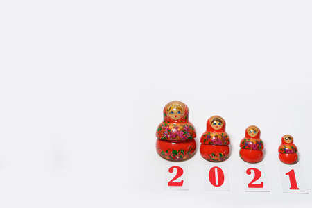 red christmas numbers 2021 combined with russian nesting dolls on isolated white background. Xmas matryoshka Holiday decoration or postcard concept with top view and copy spac