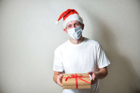happy man in a white T-shirt and Santa's red Christmas hat holds a gift with a red ribbon on hands. congratulations on christmas. holiday concept in pandemic mode. gift delivery to people.